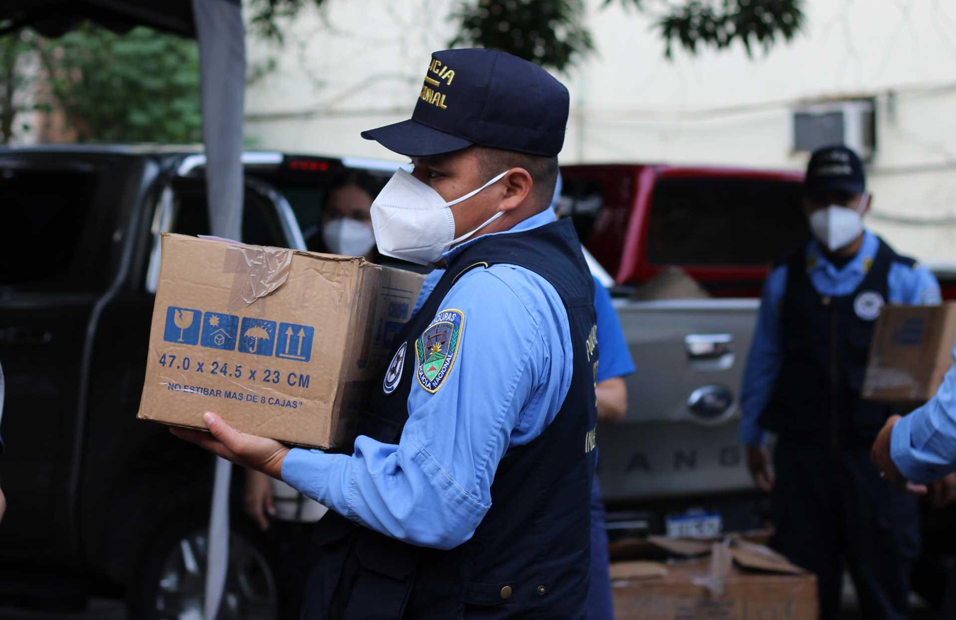 Hombre con una máscara que lleva una gran caja marrón