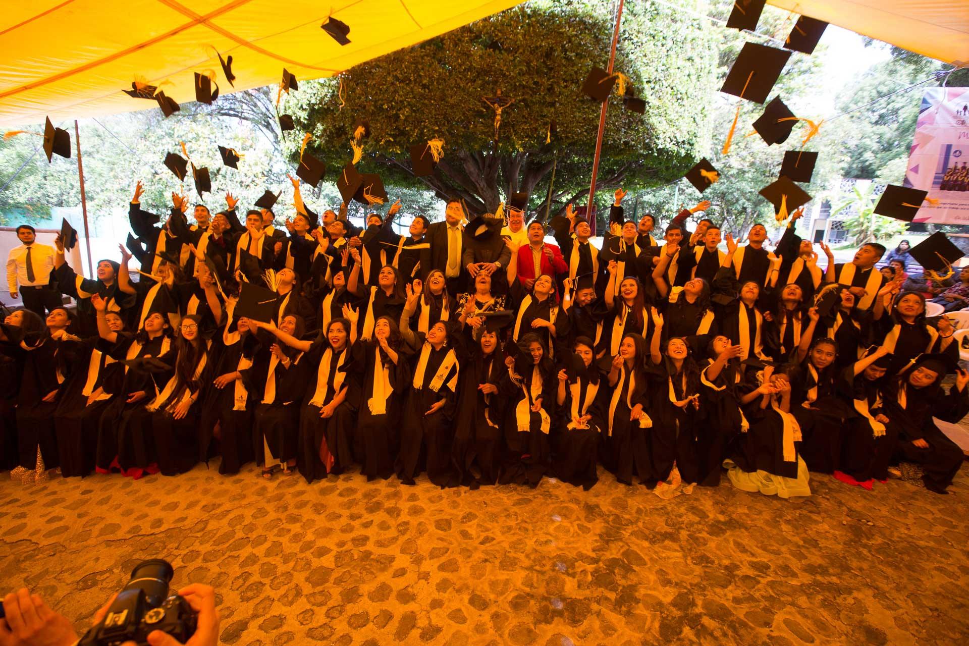 Grupo de estudiantes lanzando sus gorras de graduación al aire