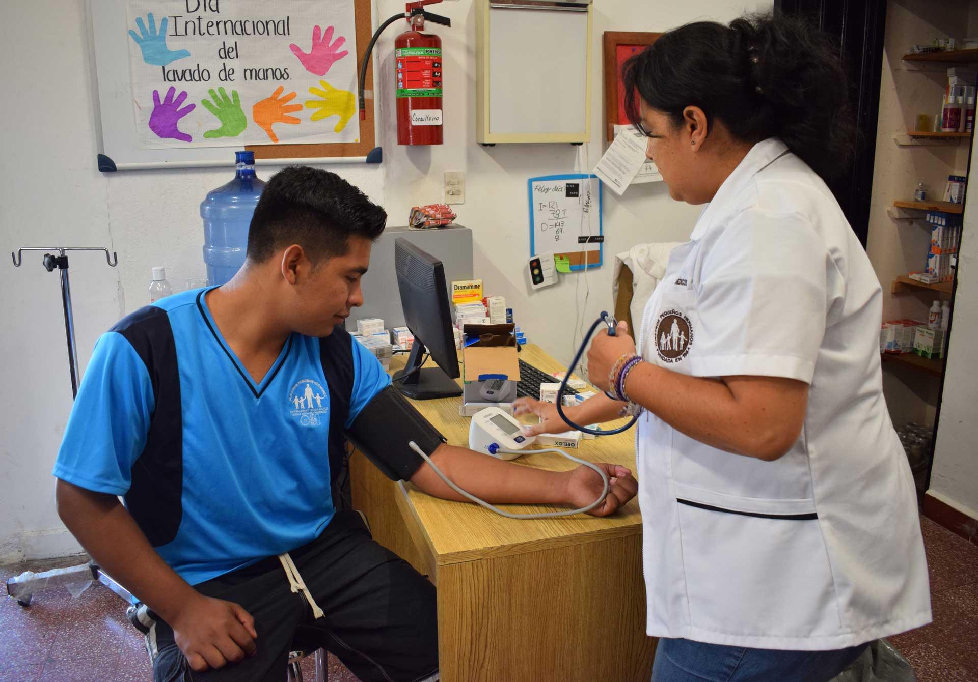 NPH brinda protección a los niños en América Latina | Joven obteniendo su presión arterial medida.