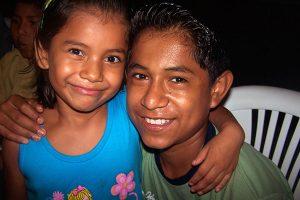 NPH Bolivia Niña con cabello oscuro hasta los hombros y un niño mayor abrazados sonriendo a la cámara.