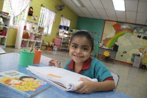 NPH El Salvador_Young girl with her hair pulled back smiling over a white workbook, holding a pencil