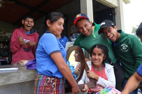 NPH Guatemala_Young woman named Maricruz surrounded by friends and family. Maricruz holds a mirror and everyone is laughing and smiling.