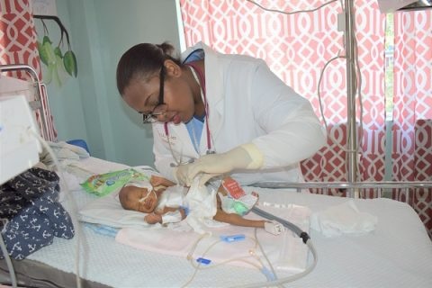 NPH Haiti_Young doctor with hair pulled into a bun attending to a premature infant attached to tubes and IVs