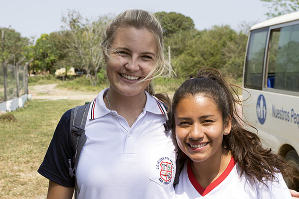 NPH Bolivia Volunteer_Smiling blond young woman in a white polo standing alongside a younger smiling brunette wearing a white shirt with a red collar in front of a white bus