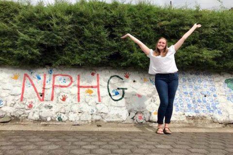 Mujer rubia con una camisa blanca y jeans con las manos levantadas en celebración frente a una pared que dice NPH Guatemala