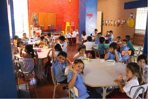 Kids sitting at a table waving, El Salvador